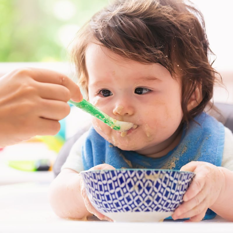 baby with blue bib and blue bowl eating veggie dish with sweet potato for babies - SuperKidsNutrition.com