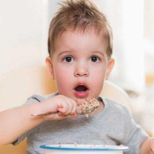 little boy eating buckwheat cereal porridge
