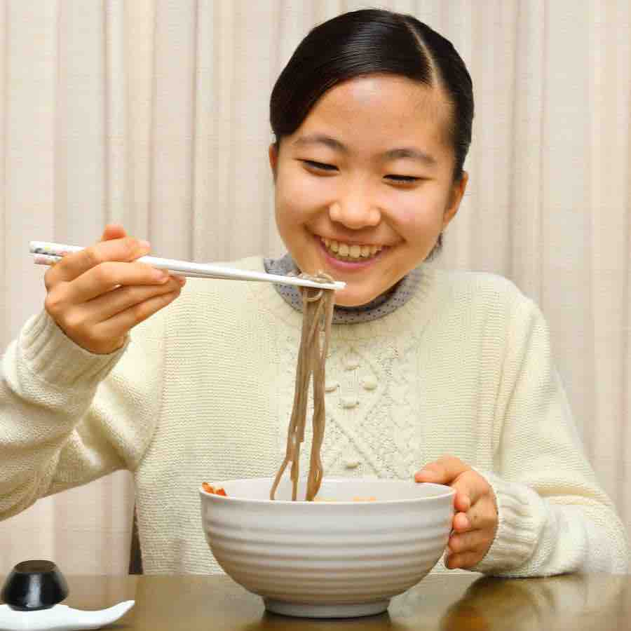 Teenager eating buckwheat soba noodles a superfood