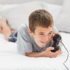 Little boy lying on bed playing video games at home