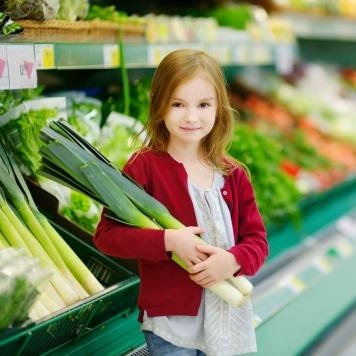 Little girl choosing a leek in a store