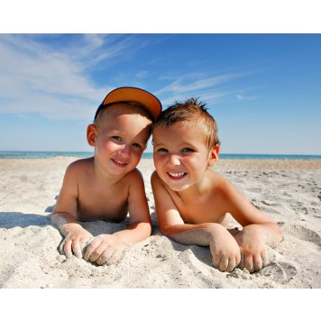 Two brothers  Lying  on the sea beach under the summer sun