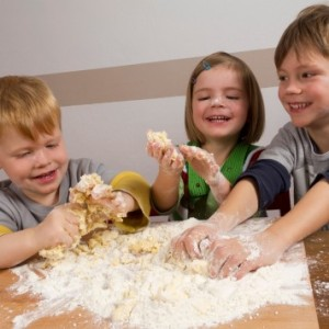 Kids making dough for baking christmas cookies