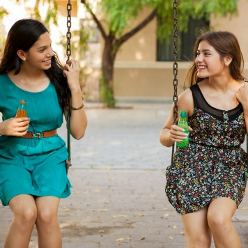 Beautiful teenage friends hanging out at a park and drinking soda