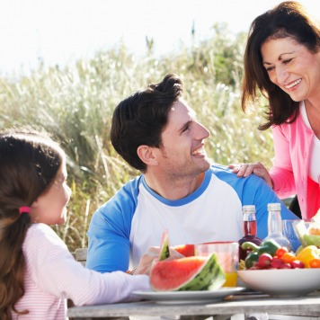 Father With Daughter And Grandmother Enjoying Outdoor Barbeque