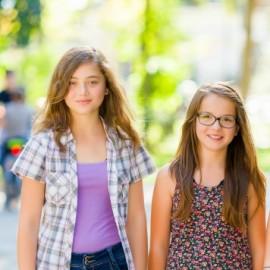 Three teen schoolgirls walking in the park