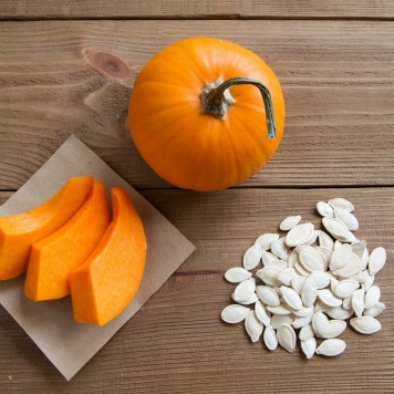 pumpkin slices on parchment paper, seeds and the whole pumpkin. wood background. top view