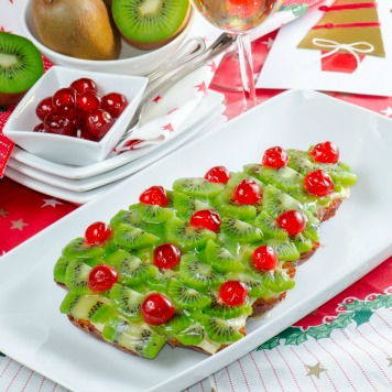 a fruitcake for happy christmas on table wth accessories for dinner