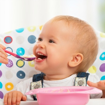 happy mother feeds funny baby from a spoon
