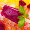Homemade frozen popsicles made with Dragon fruit on ice background