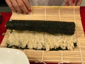 step to make sushi by rolling the seaweed with the bamboo