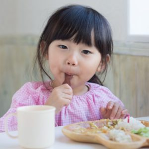 Asian Girl eating vegetables