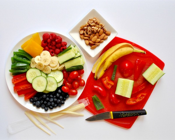 prepping ingredients for food art with fruits, veggies, and nuts on cutting board and plate