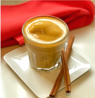 pumpkin smoothie with cinnamon sticks and red napkin for healthy Halloween recipe