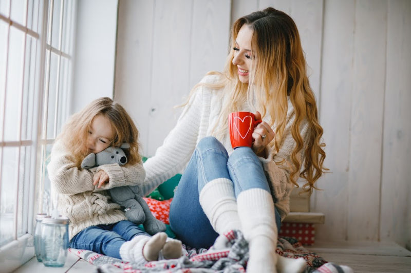 mom and daughter dressed in cozy clothes for a relaxing holiday