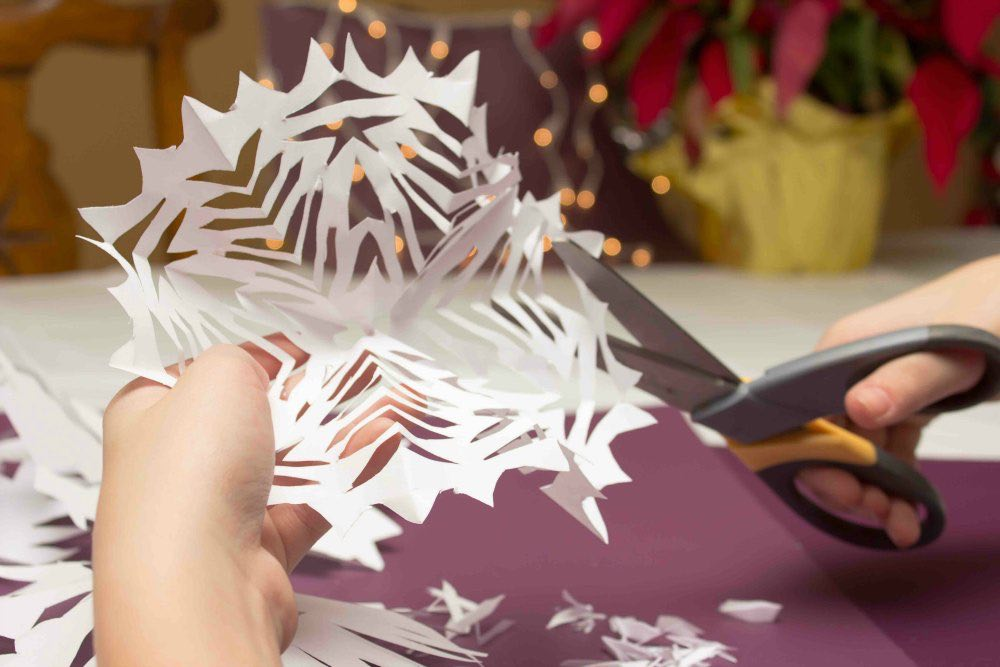 kid making snowflake out of paper