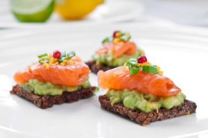 Brown bread sandwich with smoked salmon, avocado topped with chive and pepper