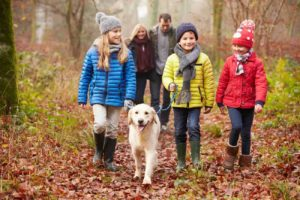 family taking hike in leaves with dog