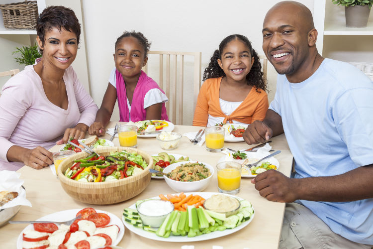 An attractive happy African American, smiling family of mother, father, two daughters eating salad and healthy food at a dining table.
