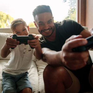 Portrait of father and son enjoying playing video game in living room. Smiling young man and little boy playing video game at home.