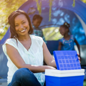 black woman sitting with blue cooler at a camp site