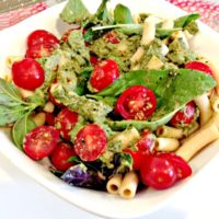 chickpea pasta with cherry tomatoes, basil, and sauce in a white bowl