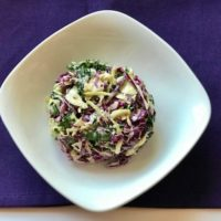 slaw made out of purple and yellow cabbage, kale, and dressing with a purple cloth underneath