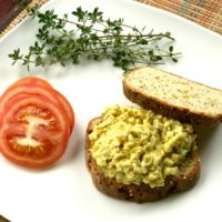 curried egg salad on millet bread with tomato and herbs