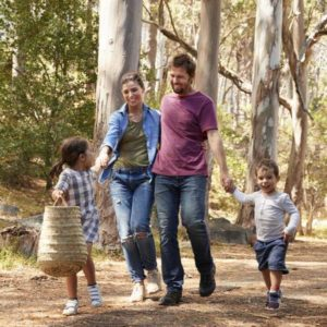 Family Walking Along Path Through Forest Together with picnic basket