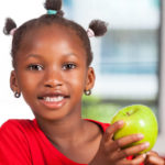 African girl at school snacking on an apple for a healthy snack
