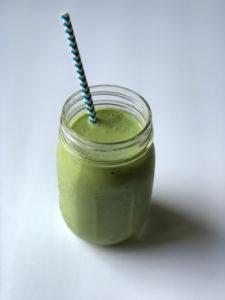green smoothie with striped straw in mason jar