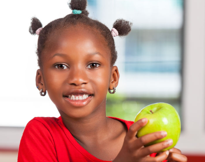 African girl at school with apple in hand.