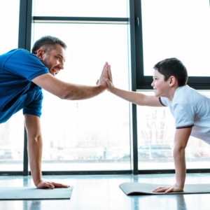 father and son doing high five sign while doing push up exercise for indoor games for kids