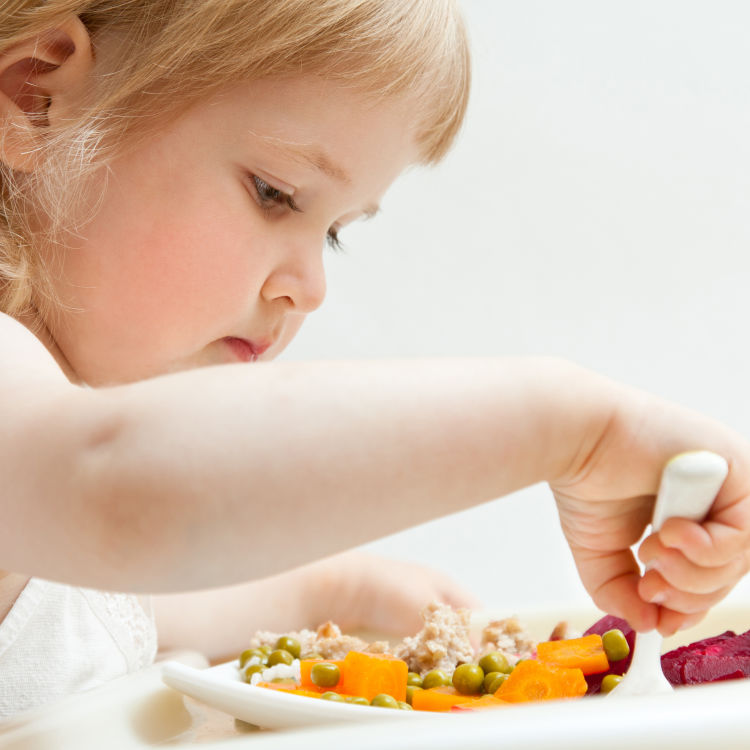 Adorable baby girl picky eater eating fresh vegetables; healthy eating for a baby