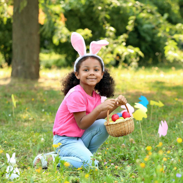 little girl collecting eggs in her easter basket