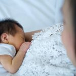 Asian mother holding her newborn daughter while breastfeeding child on the bed