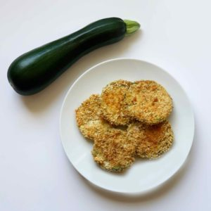 Crispy Baked Zucchini Chips on plate with whole zucchini