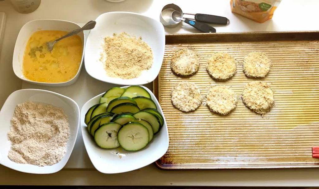 process of making zucchini chips with egg, breadcrumbs, and flour