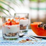 healthy greek yogurt and papaya parfait in glasses. Outdoor background.