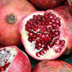 Open pomegrante shows seeds on top of a pile pomegranates