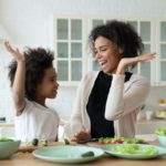 Excited African mom give high five gesture to little adorable mixed-race daughter family cook together dinner healthy food vegetarian salad. Teach kid, happy motherhood, share cookery skills concept to prevent colon cancer starting young